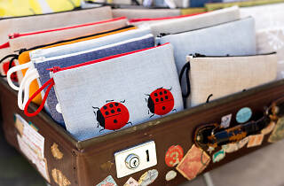 A suitcase with stickers and pins on it full of cute embroidered purses.