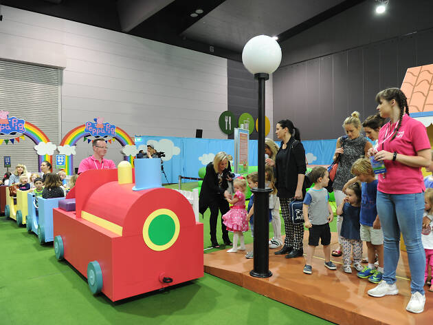 Kids and adults about to get on a toy train at the Peppa Pig Playdate experience.