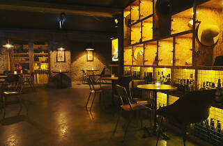 Soultrap bar's seating space and shelving in a low light.