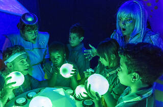 Kids and performers gazing in awe at glowing green orbs