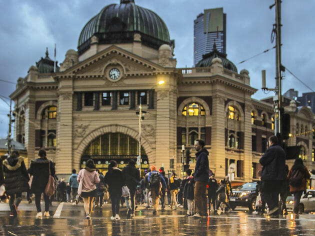 People crossing intersection on a rainy day at Flinders Street Station