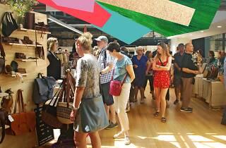 People walking through market stalls indoors.