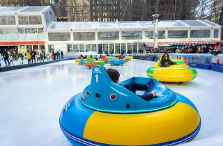 People riding in round cars on an ice rink.