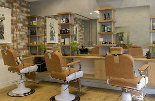 Barbershop with cream seats, mirrors and an exposed brick wall.