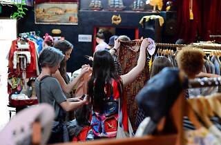 People shopping at a colourful clothing market.