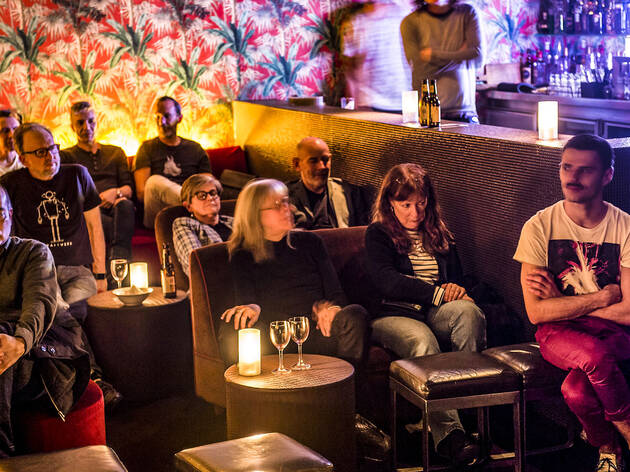 People sitting in lounges inside a venue at Classic Album Listen