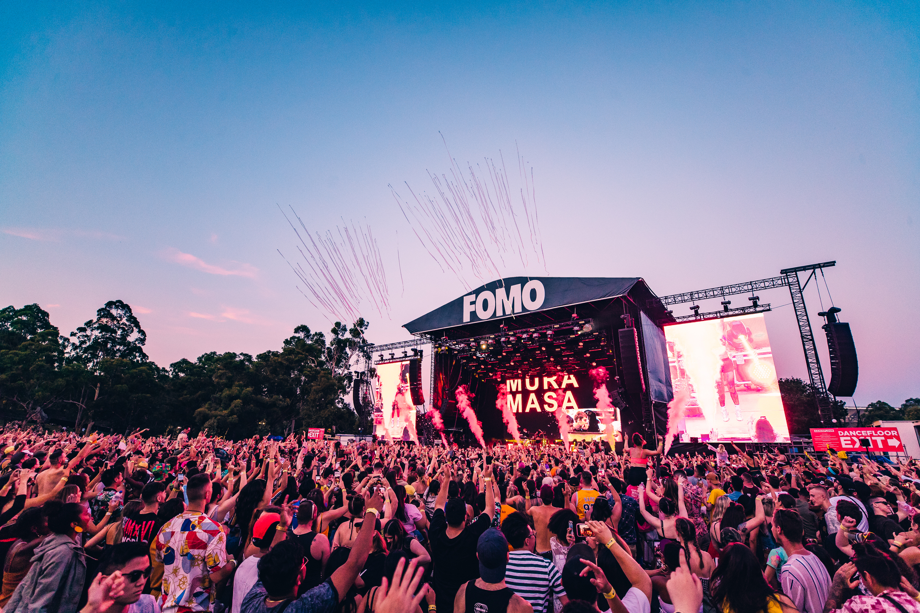 Crowd of people dancing at FOMO Festival as the sun sets.
