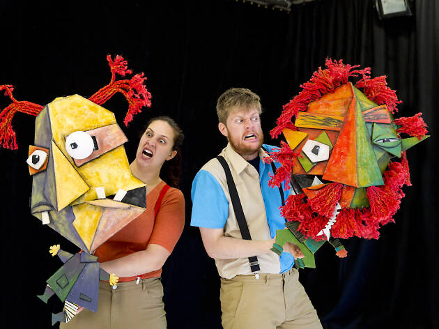 Two actors holding colourful puppets in front of a black wall
