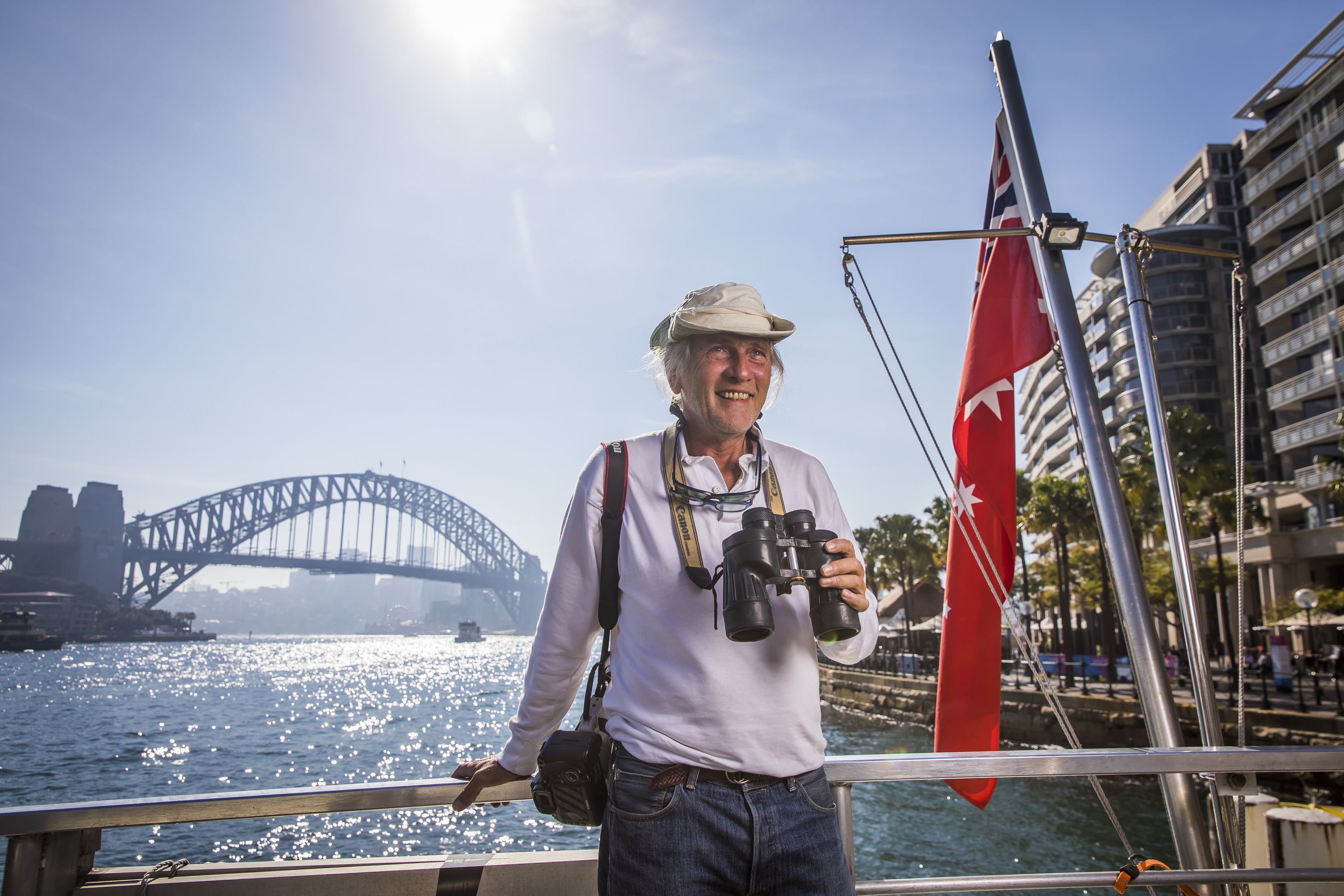 Biggles, Oz Whale Watching tour guide, standing on a boat by Sydney Harbour