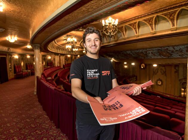 Cristian Speranza, Sydney Film Festival volunteer, handing out film festival guides inside the State Theatre, Sydney