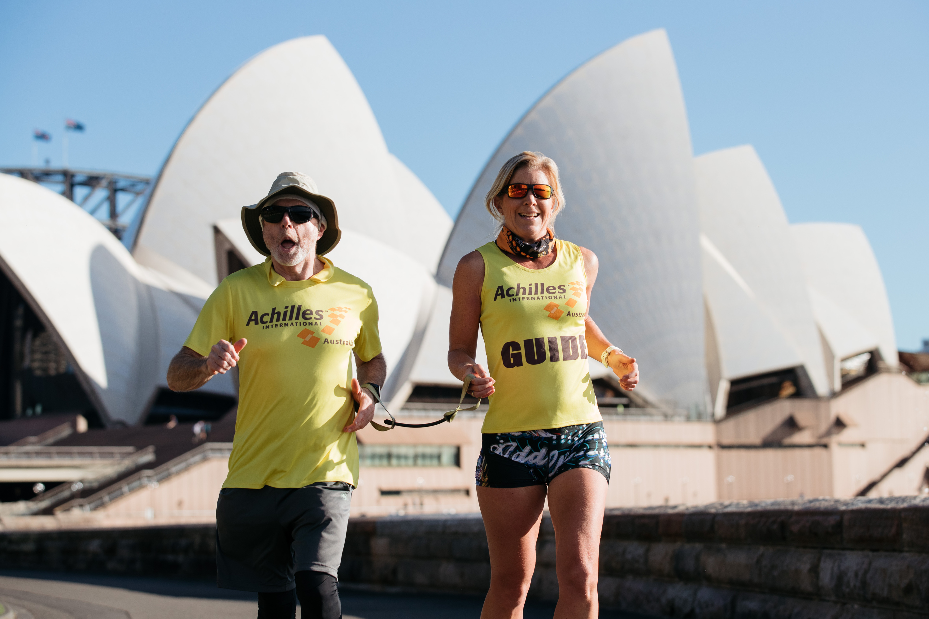 Achilles Running Club runners Stephen Green, a vision impaired runner, and Julia Wenner, his guide, running in Sydney Botanic Gardens with the Opera House in the background