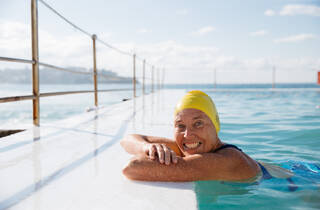 Nicki Vinnicombe, a swimmer at Bondi Icebergs, resting her arms on the side of the pool wearing a yellow swim cap