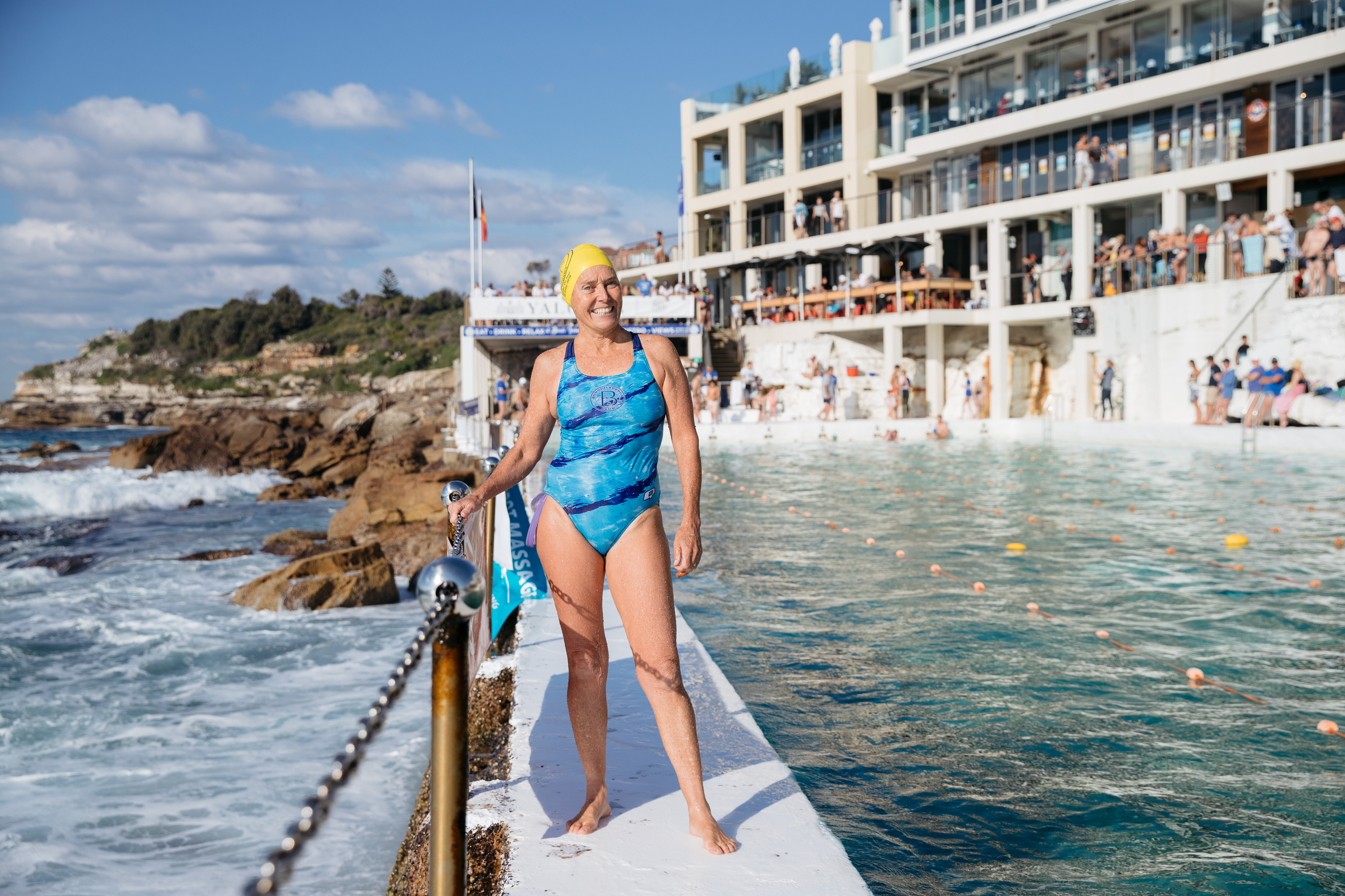 Nicki Vinnicombe, a swimmer at Bondi Icebergs, standing on the side of the pool wearing a yellow swim cap and blue swimming costume