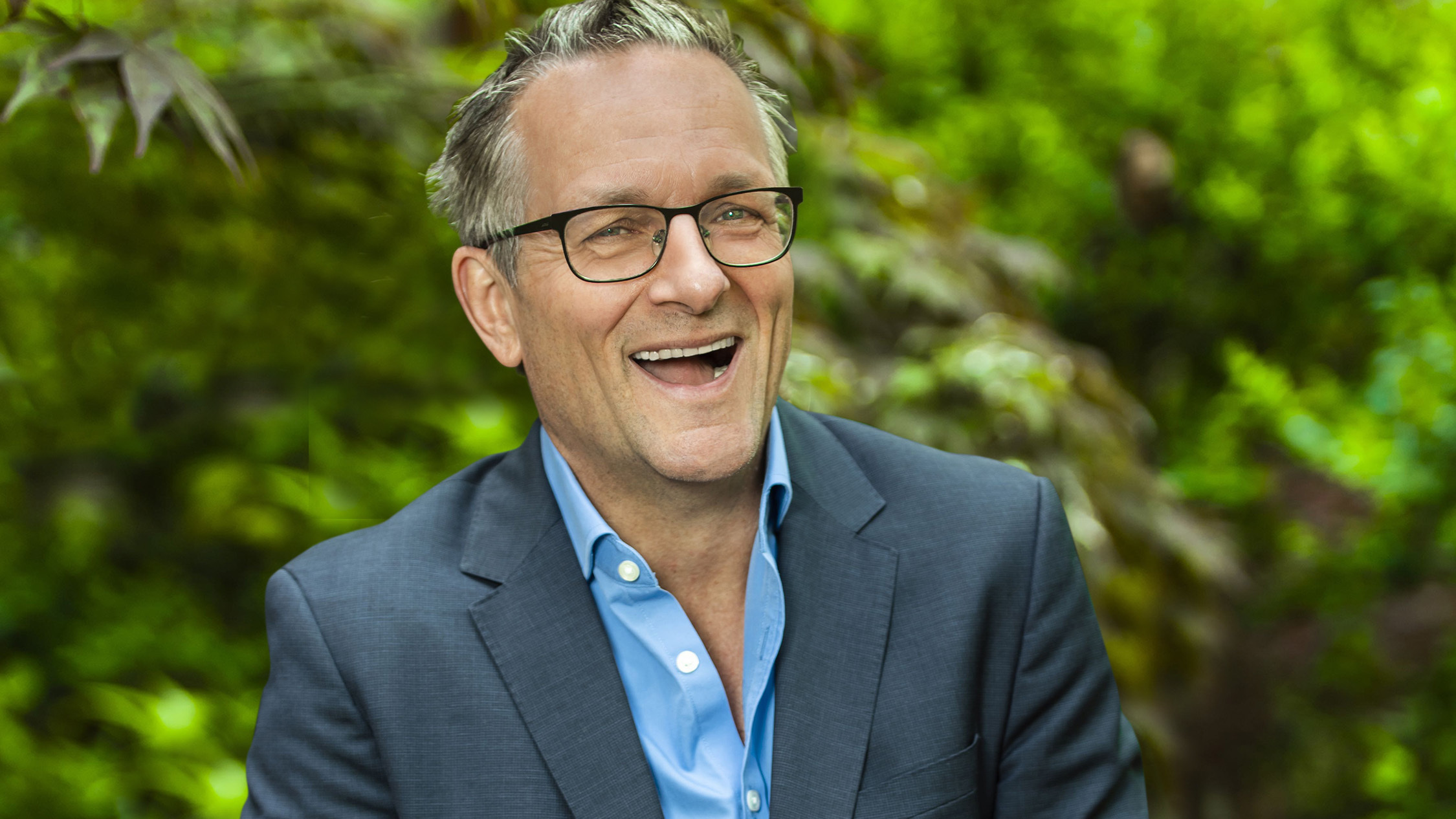Michael Mosley smiling in front of some trees.
