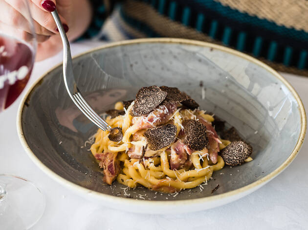 A plate of pasta with black truffles on top