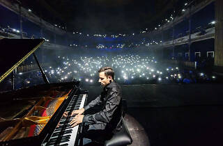 Peter Bence playing the piano to an audience with