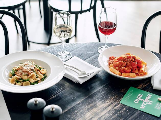 Two bowls of pasta on a table with wine