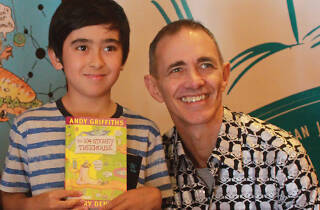 Andy Griffiths and a child with a book.