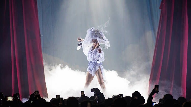FKA Twigs on stage wearing a white Mary Magdalene inspired costume