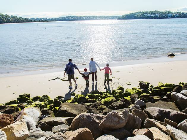A family walking on the beach at Bonnie Vale Bundeena in the Royal National Park.
