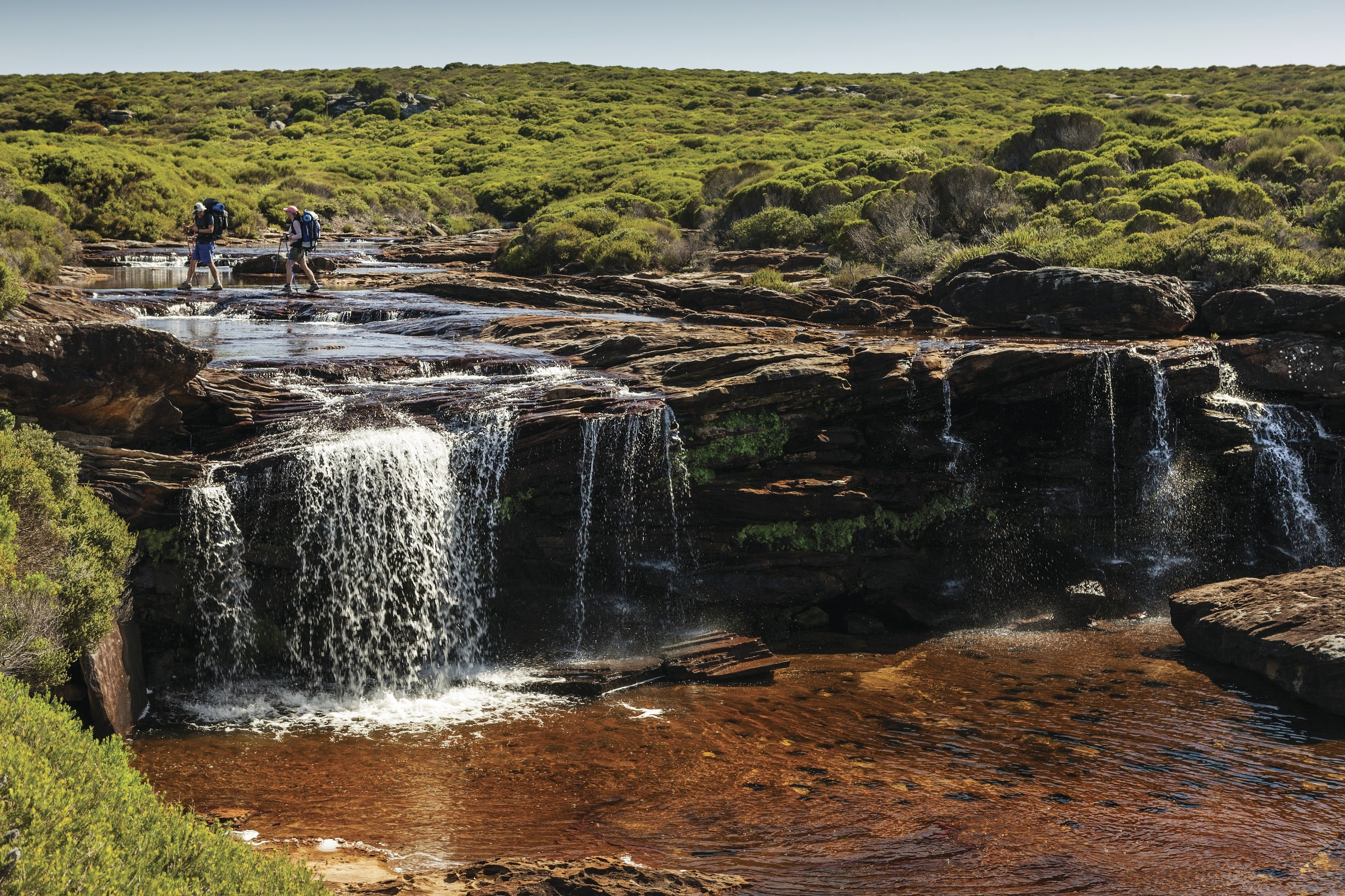 Bushwalkers walking near the edge of a rocky waterfall in the Royal National Park.
