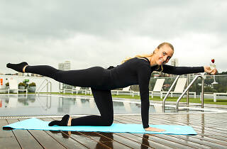 Woman in a black leotard doing a pilates pose and drinking prosecco.