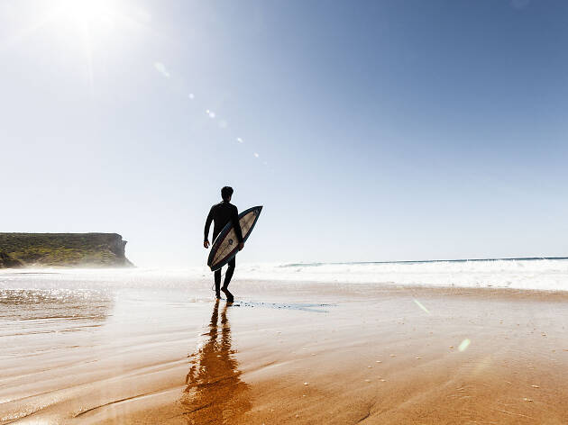 A surfer with a board walking on Garie Beach in the Royal National Park.