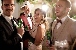 People dressed in 1920s outfits drinking.