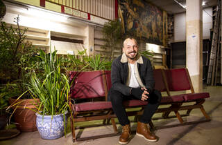 Commune founder Sam Ali sitting at the Newtown venue, smiling and sitting on cinema-style chairs