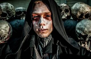 An actor in scary make-up with fake skulls behind them.