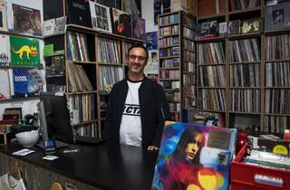 Owner of Repressed Records stands smiling behind the cashier desk