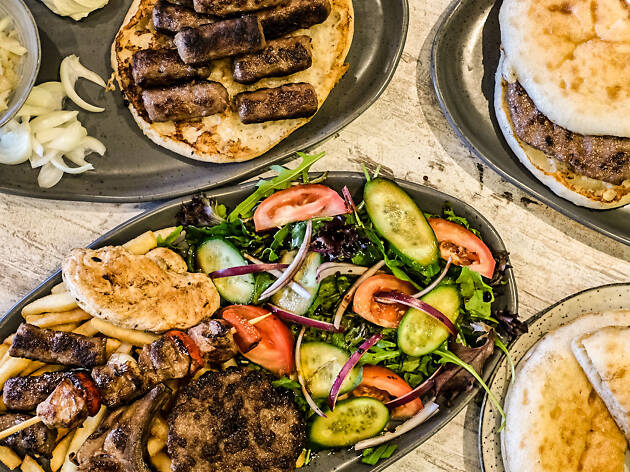 Plates of cevapi sausage, garlic salad, lepinja bread and a mixed grill