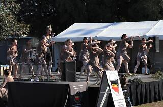 Young Indigenous dancers in traditional dress from Redfern Dance Company dance on stage.