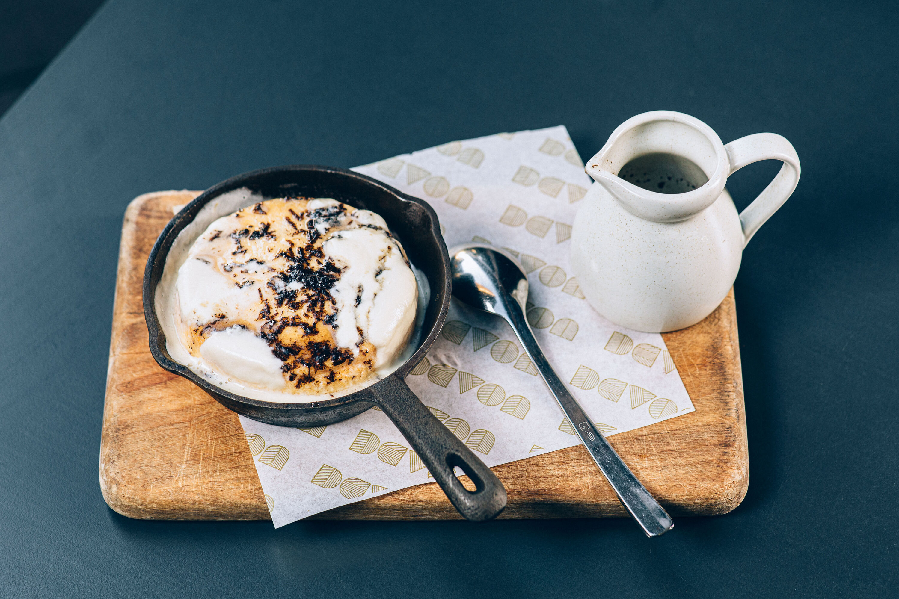 Truffle hotcakes in a pan, presented on a wooden chopping board with jug of sauce