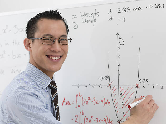 Mathematician Eddie Woo smiling and writing on a white board.