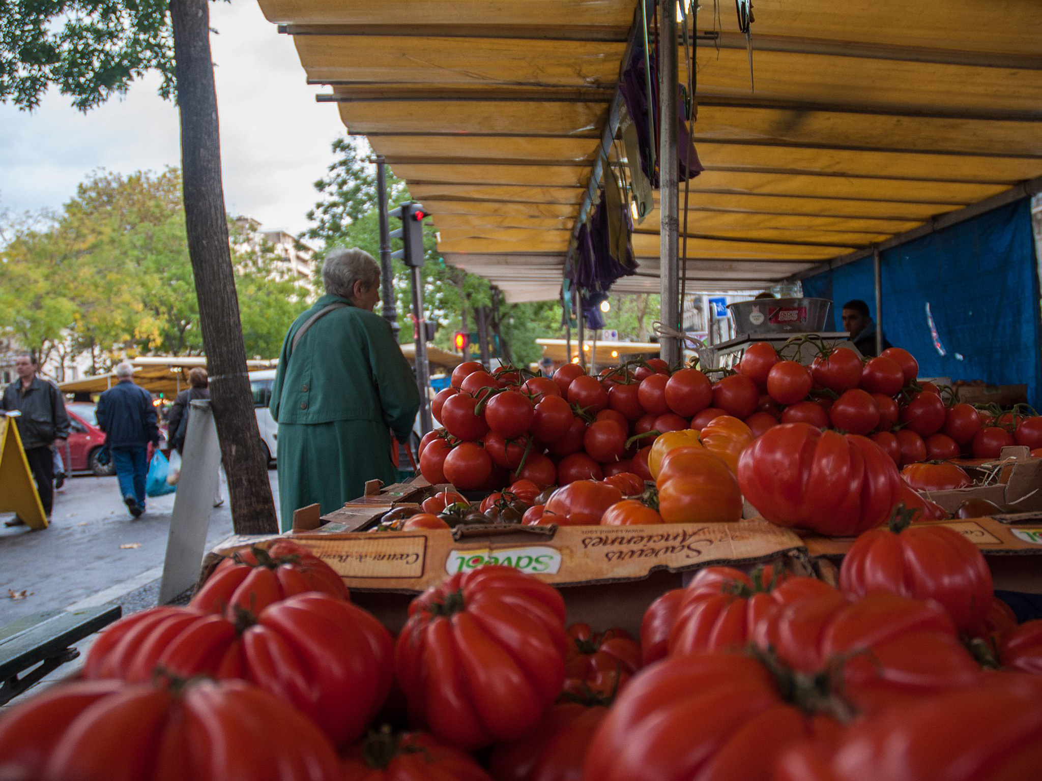 An elderly woman browses a fruit and veg stand at the Marché Bastille