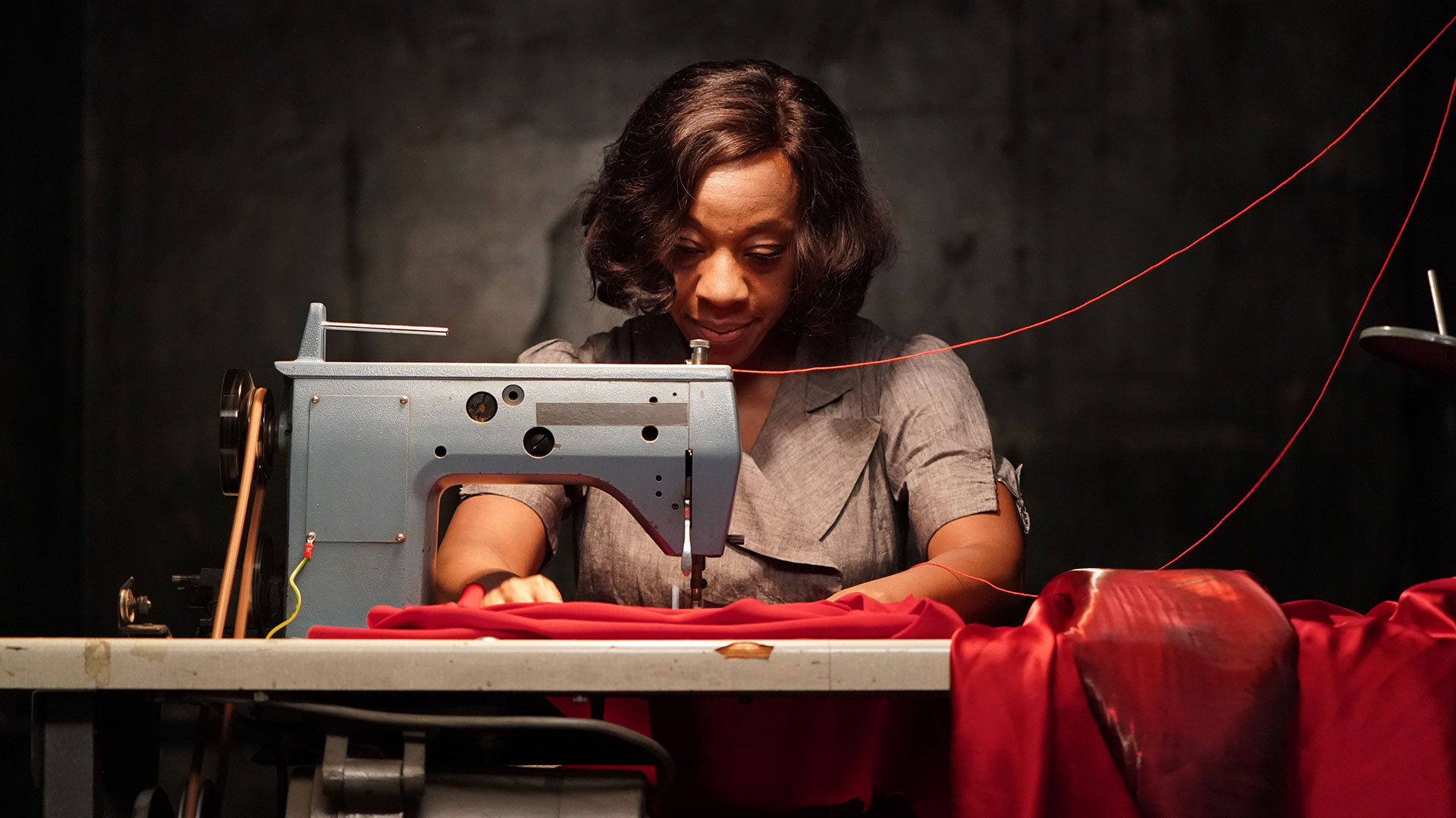 Marianne Jean-Baptiste works on a haunted dress with her sewing machine