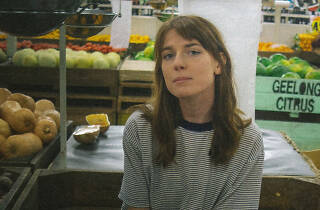 Melbourne artist Angie McMahon sitting outside a fruit shop in a striped t-shirt.