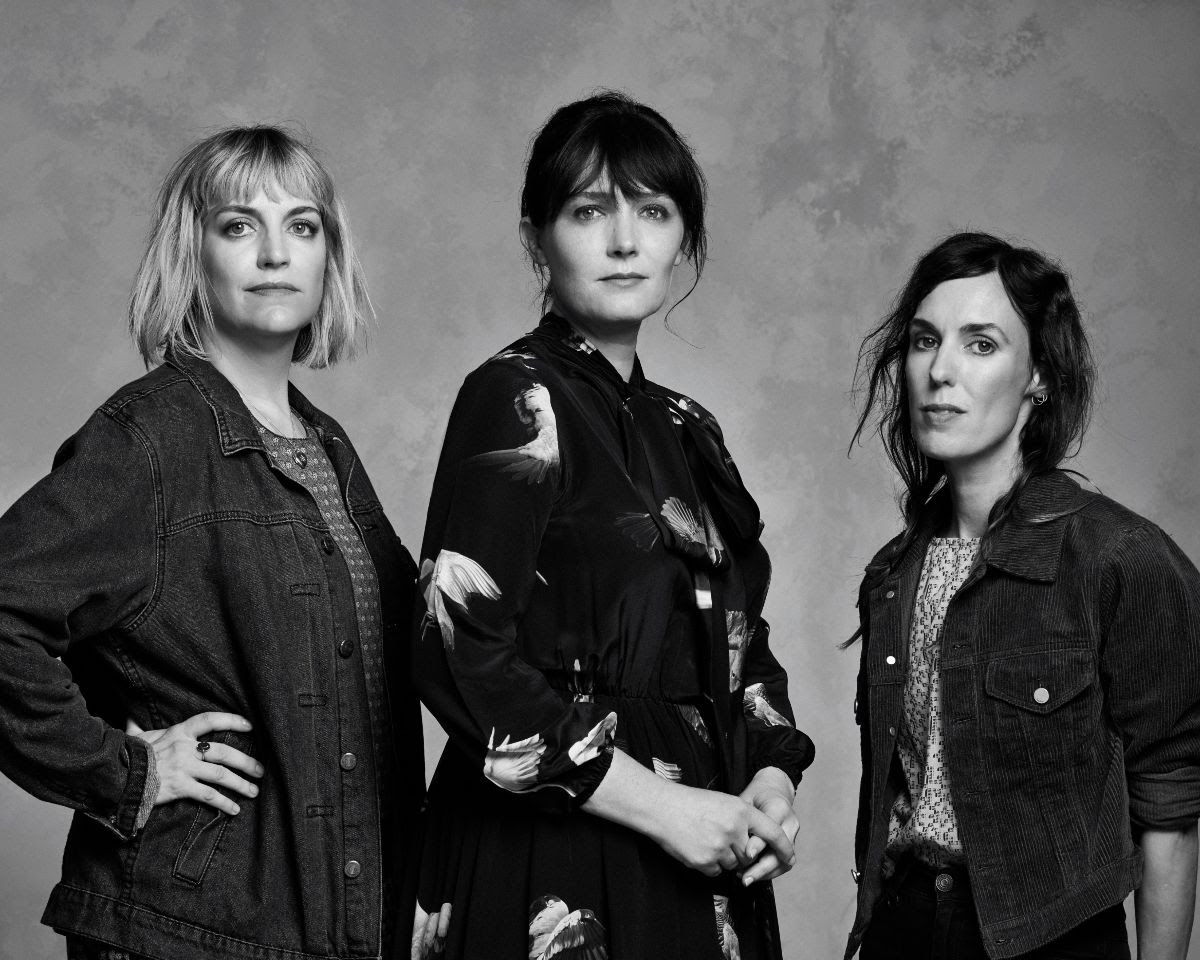 From the left: Sally Seltmann, Sarah Blasko and Holly Throsby in black jackets facing shoulder first towards the camera