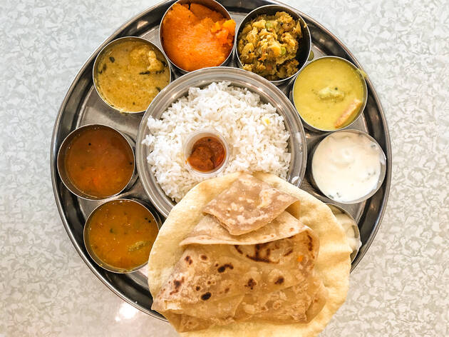 A thali plate with curries, rice and naan