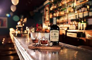 Two cups and a bottle of Jameson Cold Brew on a bar.