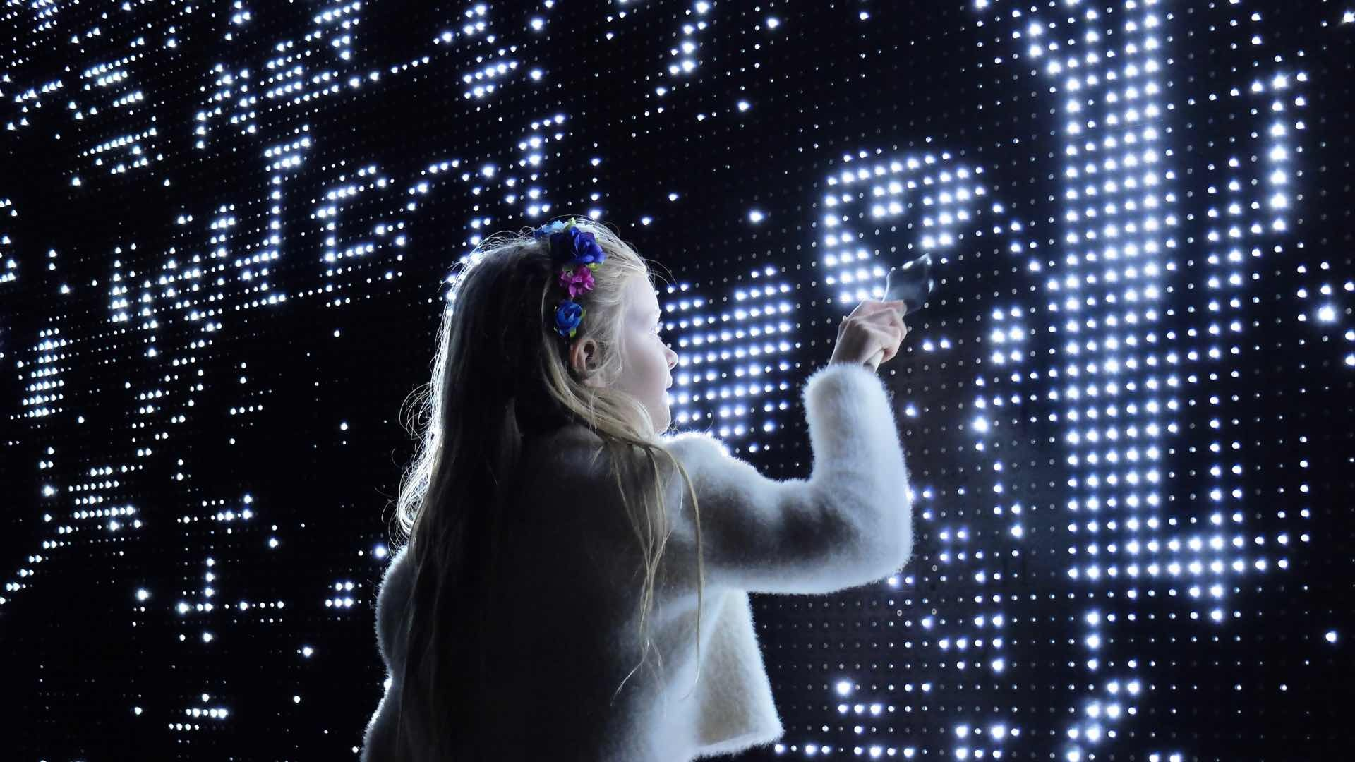 Small girl interacting with the Waterlight Graffiti installation