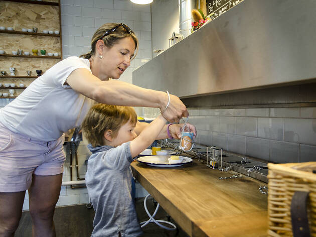 Two people making breakfast at Eggs & Bread
