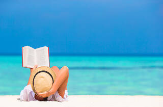 Una noia llegint en una platja tropical