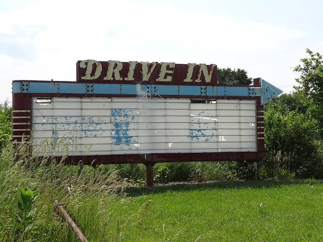 An old sign for a drive in movie theater