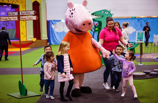 Kids playing with a person in a giant Peppa Pig costume.