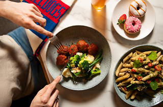 A plate of meatballs being cut into next to a plate of pasta and a plate of doughnuts