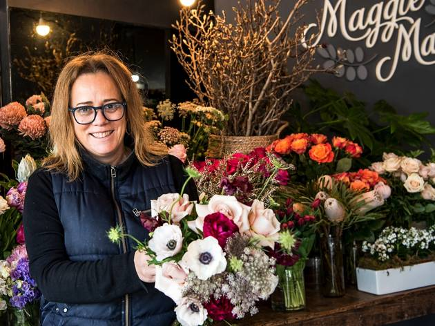 Person holding flowers at Maggie May Florist Flower Store
