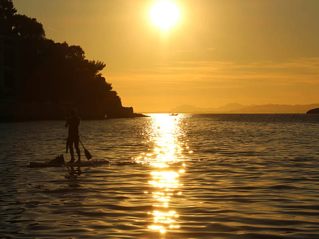A paddle-boarder in a cove near Saint-Jean-Cap-Ferrat