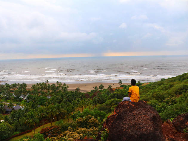 A man looks down at the sea from a hill in Goa